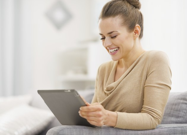 Smiling young woman sitting working on tablet pc