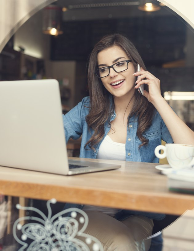 Woman talking by mobile phone and using laptop at cafe
