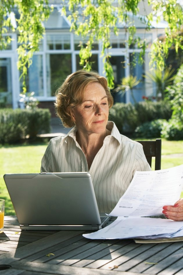 Senior woman sitting in garden with laptop, looking at paperwork