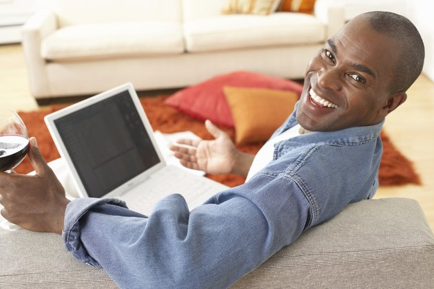 Mature man on sofa with laptop, smiling, portrait