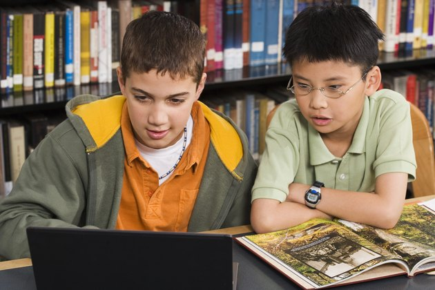 Boys using laptop in library