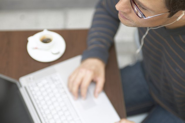 """""""Man sitting at cafe table using laptop computer, close-up"""""""
