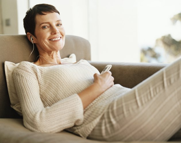 Mature Woman Lies on a Chaise-Lounge Wearing an Earpiece and Holding a Mobile Phone