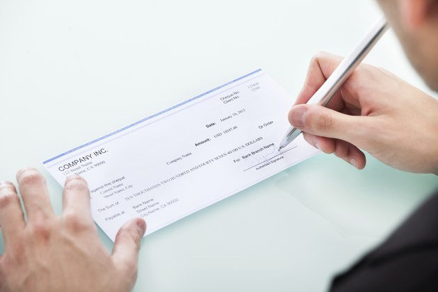 Businessman Signing On Cheque