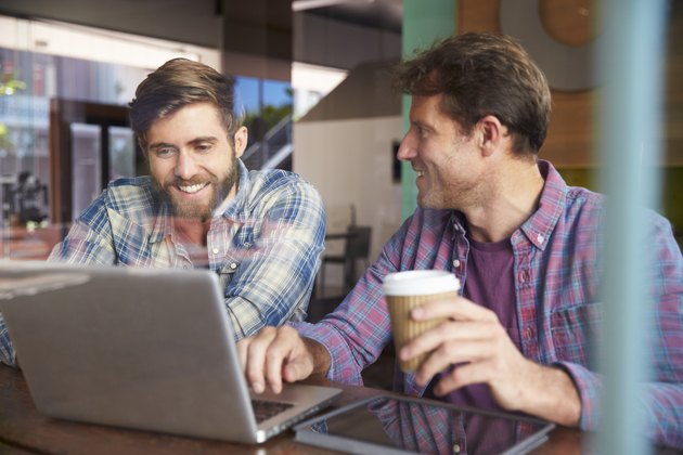 Two Businessmen Working On Laptop In Coffee Shop