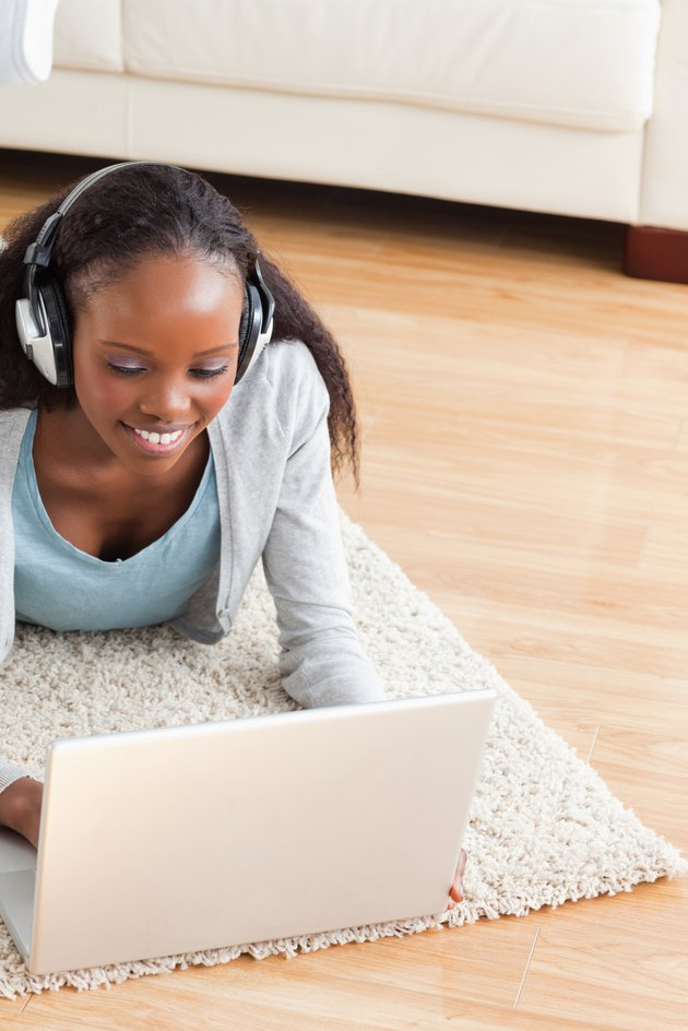 Close up of woman lying on floor with laptop listening to music