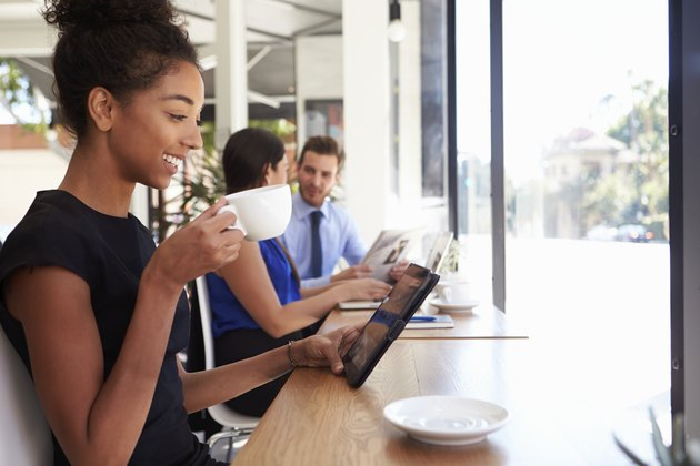 Businesswoman Using Digital Tablet In Coffee Shop