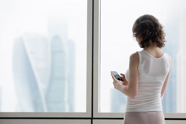 Young woman using smartphone indoors