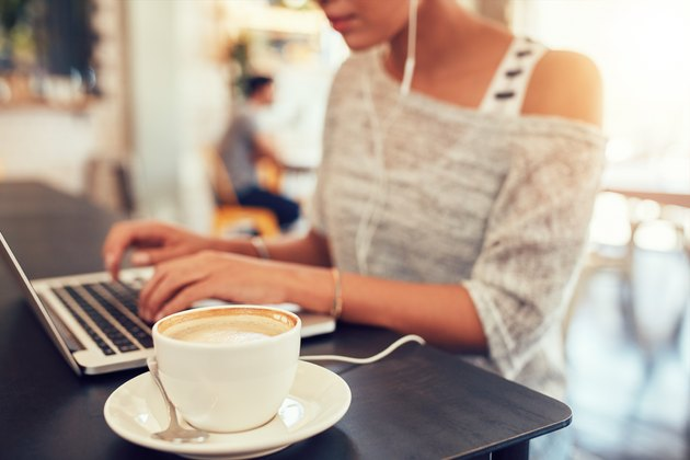 Cup of coffee on cafe table with a woman