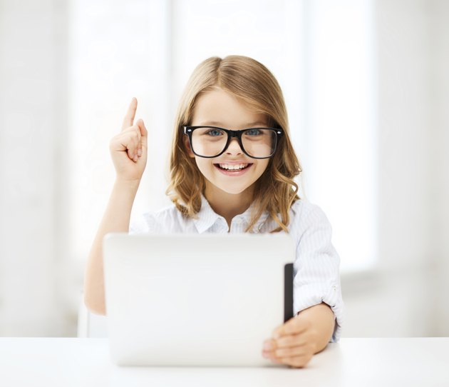 smiling girl in glasses with tablet pc at school