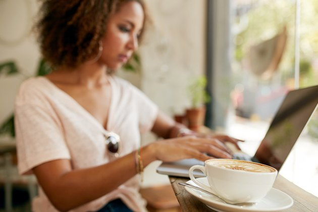 Fresh cappuccino with a woman using laptop in cafe