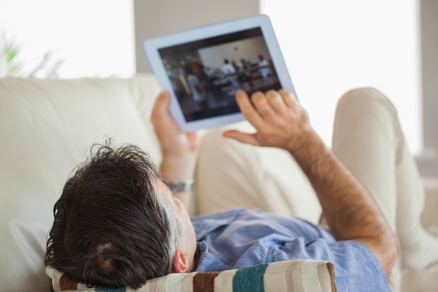 Man laying on a sofa using a tablet pc