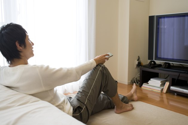 Man sitting on floor and watching TV