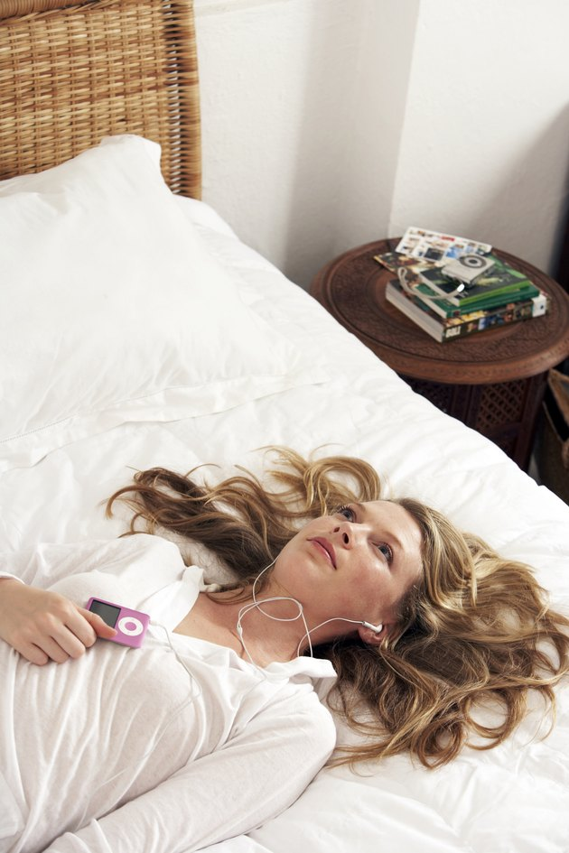woman lying on a bed listening to music