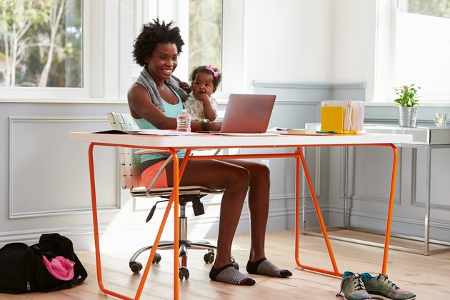 Woman holding child using computer at home after exercising
