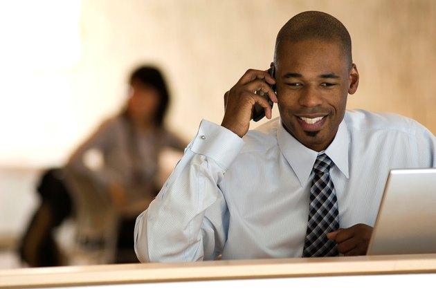 African-american businessman talking on PDA smart phone.
