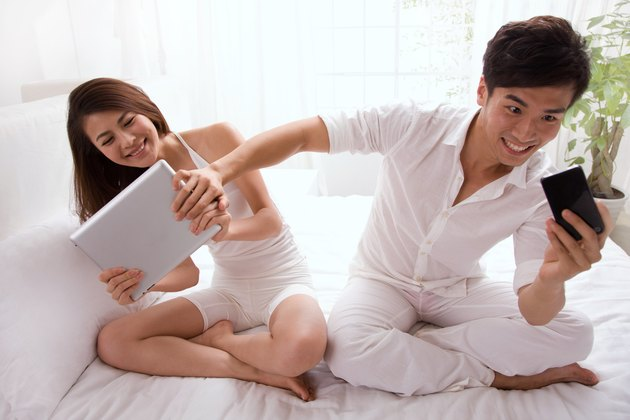 Young couple watching cell phone and tablet computer on bed