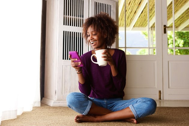 Smiling woman sitting on floor at home with cell phone