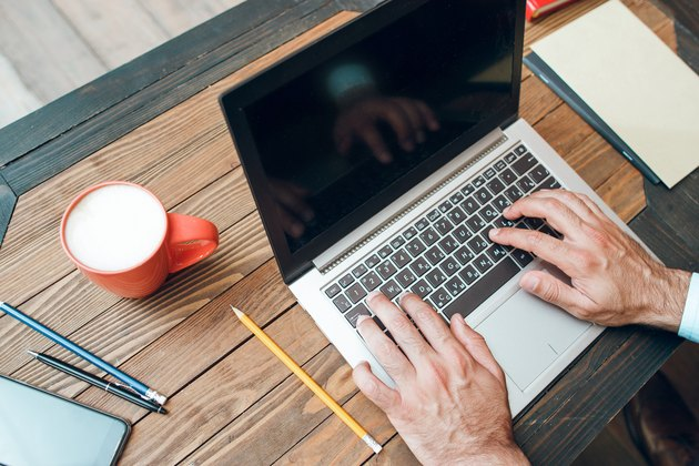 Male hands typing on laptop keyboard, mockup