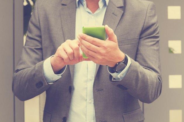 Elegant man using cellphone outdoors.