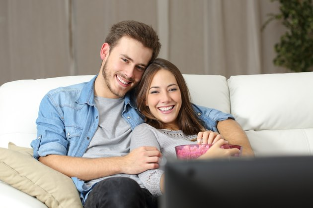 Happy couple watching movie on tv