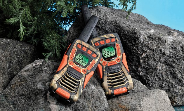Photo of a pair of Cobra CXT 1035 FLT CAMO  two-way radios in a rocky setting.