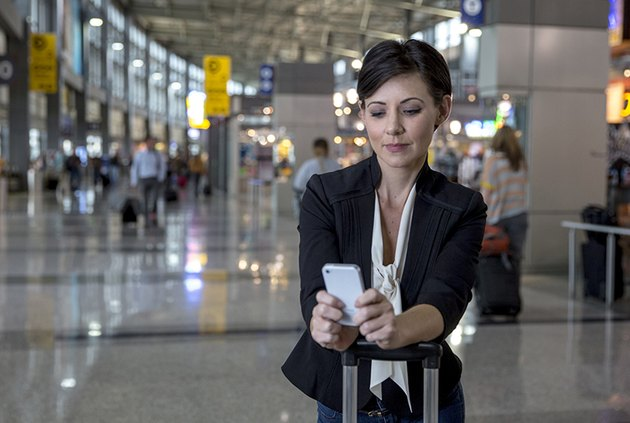 Woman texting at an airport