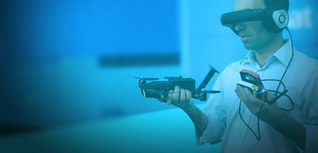 Photo of a man wearing first-person video goggles while holding UVify's Draco racing drone.