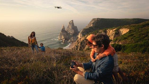 A family flies DJI's Mavic Pro drone above a scenic seaside overlook.