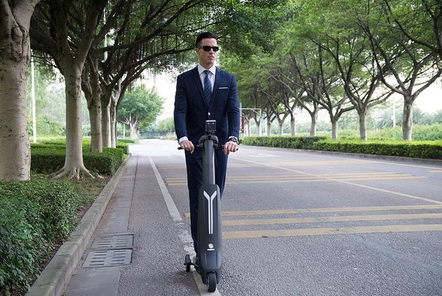 Man in suit ride electric scooter