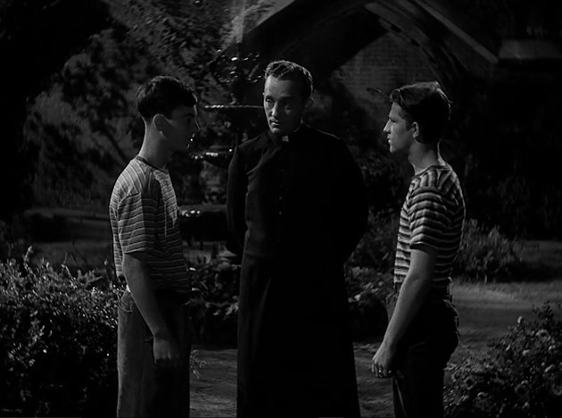 Still of Father O'Malley standing between two boys.