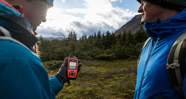 Photo of two outdoor adventurers looking at their Garmin inReach global satellite communications device.