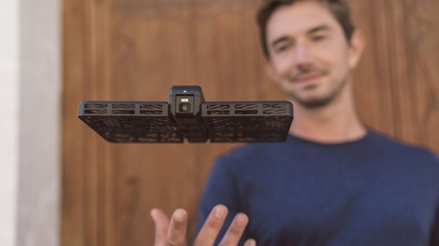 Photo of a man launching the Hover Camera Passport to hover and take photos.