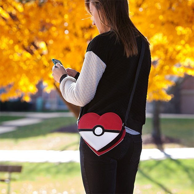 Photo of woman wearing heart-shaped Pokémon bag while texting outside.