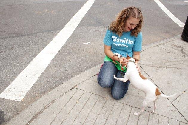 Woman kneeling down to pet dog