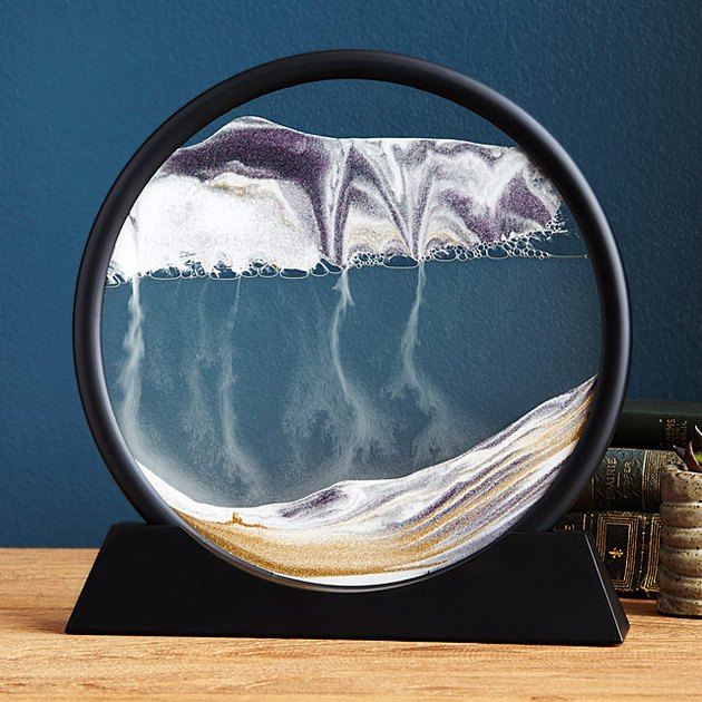 Photo of moving sand art in a black circular container.