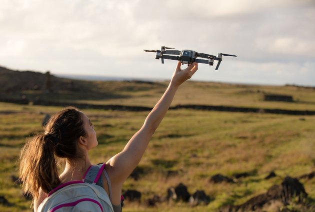Photo of a girl in a large field launching DJI's Mavic Pro drone into the air.