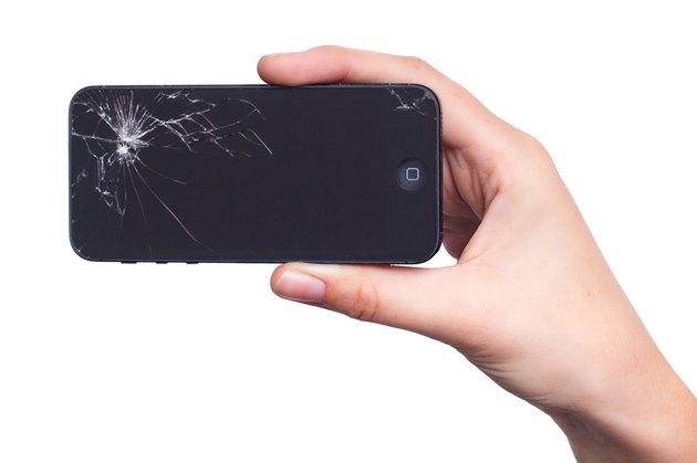 Hand holding broken iPhone
